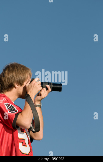 Young man , amateur hobbyist photographer, taking photograph with DSLR digital camera on a clear blue sky day, UK - Stock Image