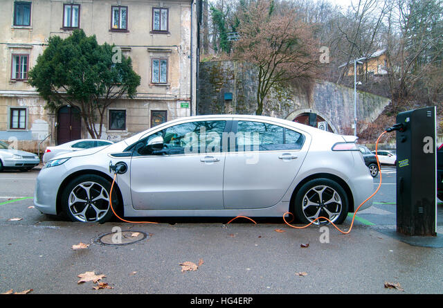Electric car, parked and charging a battery - Stock Image