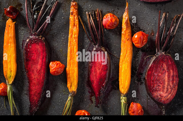 Baked carrots and beets with tomatoes - Stock Image
