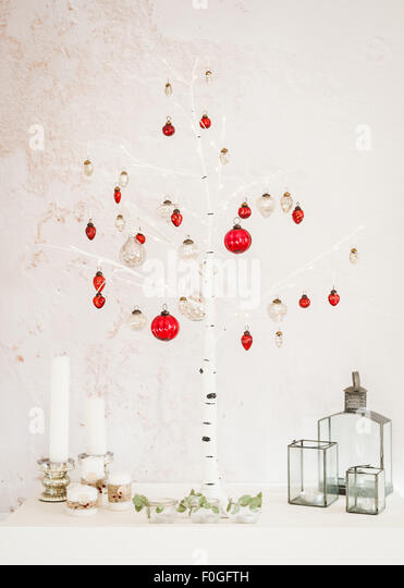 Christmas decorations at home - birch Christmas tree, candles, lanterns, silver and red mercury glass baubles, tealights - Stock Image