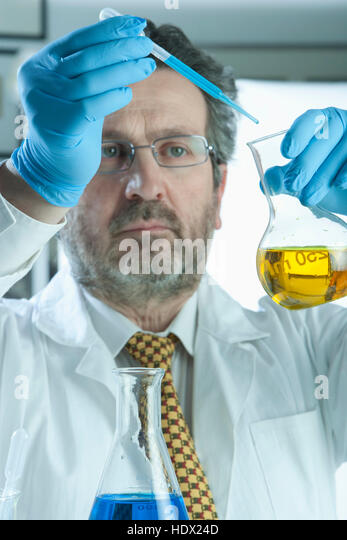 Caucasian scientist mixing liquid in laboratory - Stock Image