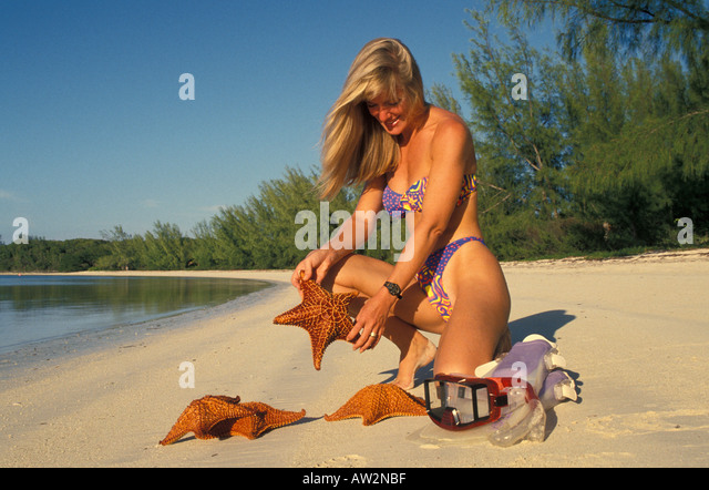 Beach woman kneeling holding starfish on beach with casuarian trees - Stock Image