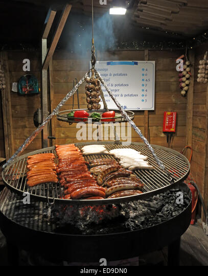 Sausage BBQ at Manchester city Xmas German markets Nov/Dec, England, UK - dusk - Stock Image