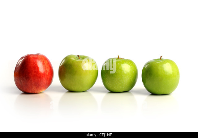 Red apple among green apples isolated on a white background - Stock Image