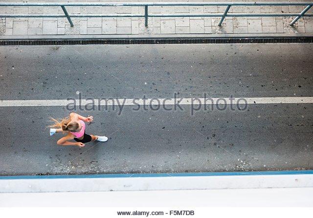 Overhead view of young female runner running along walkway - Stock-Bilder