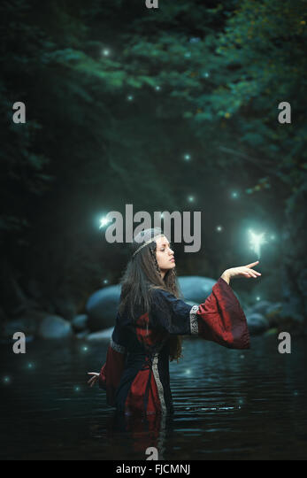 Medieval dressed woman in fairy land stream . Fantasy and surreal - Stock-Bilder