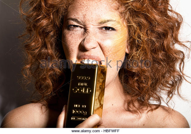 Young Woman biting gold bar - Stock Image