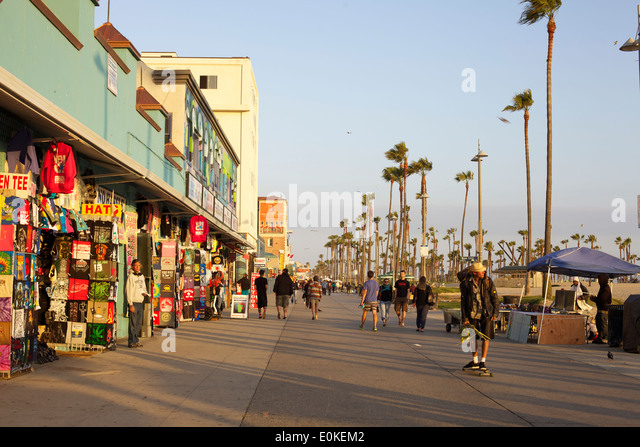 Shoppers walk and a young man skateboards down the sunny Venice Beach Boardwalk in Los Angeles, California. - Stock Image