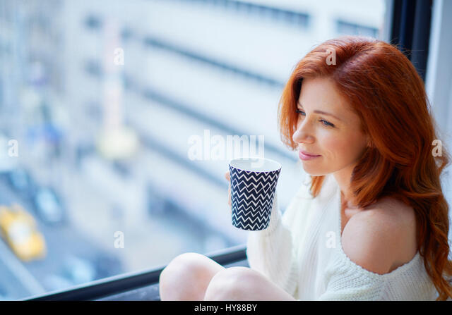 Young women with hot drink sitting by a window in New York apartment - Stock Image