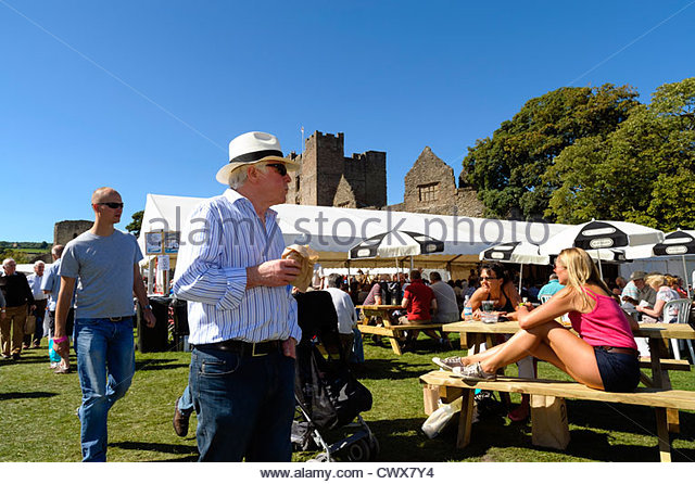 Ludlow food festival, Shropshire, UK. People enjoying sitting in the Castle grounds at Ludlow food festival. - Stock Image