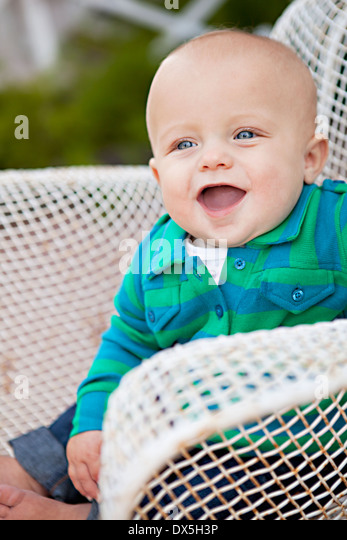 Laughing baby boy  with mouth open in wire chair, looking away - Stock Image