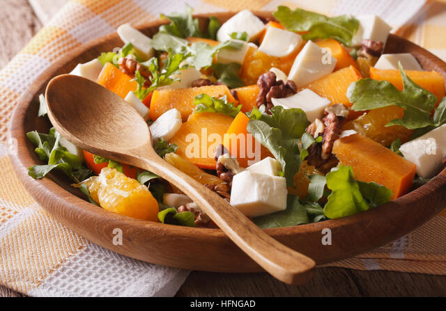 Fresh salad with persimmons, walnuts, arugula, cheese and oranges close-up. Horizontal, rustic - Stock Image