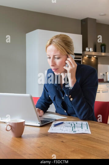 Woman working at desk - Stock Image