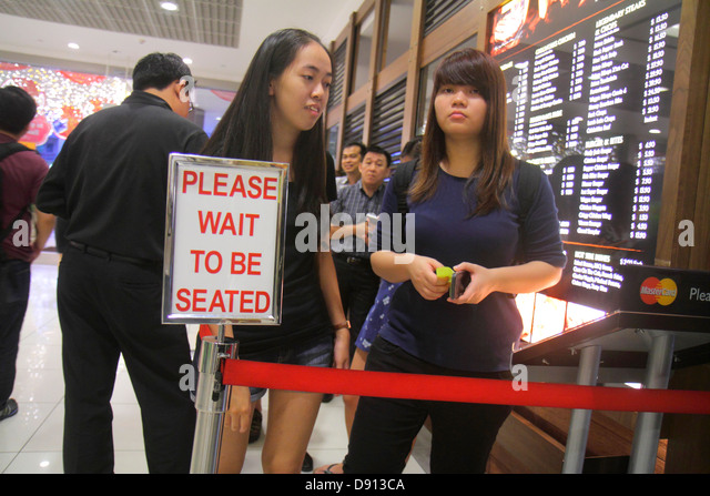 Singapore City Square Mall shopping restaurant line queue sign please wait to be seated Asian woman - Stock Image