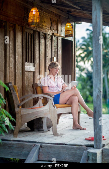 Woman relaxing with digital tablet on holiday apartment porch, Ubud, Bali, Indonesia - Stock Image
