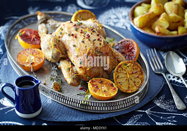 Roast chicken with glazed citrus fruits on serving tray - Stock Image