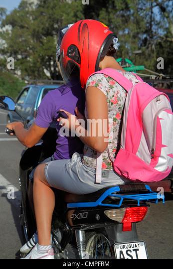 Uruguay Montevideo Avenida General Fructuoso Rivera Hispanic teen girl helmet mobile cell phone smartphone passenger - Stock Image