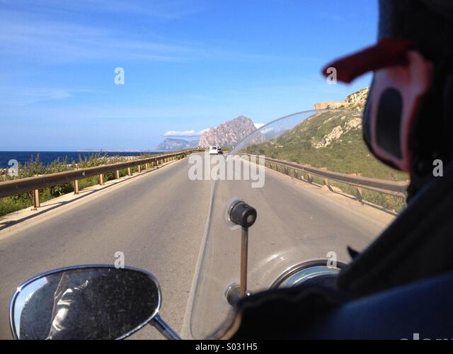 Driving motorbike at sea coast road - Stock Image