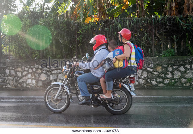 Dangerous transportation practice: a couple rides a motorcycle with a child in between them. The boy wears the primary - Stock-Bilder