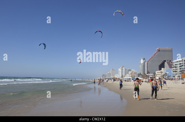 Young adults cooling down after a run with kites and kite-surfers in the background, Tel Aviv, Israel - Stock Image