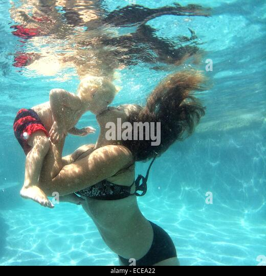 Mother kissing baby boy underwater - Stock Image
