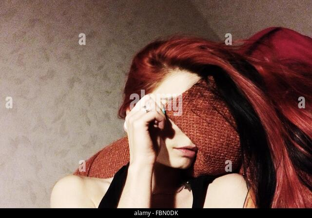 Young Woman Resting On Sofa While Covering Face - Stock Image