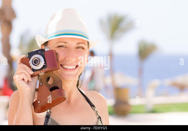 Young happy woman with healthy teeth having fun with old photo camera at the summer beach holidays. - Stock Image
