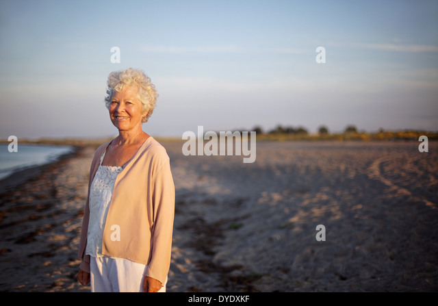 Portrait of relaxed elderly woman standing at the beach. Happy old lady standing alone on the beach with lots of - Stock Image
