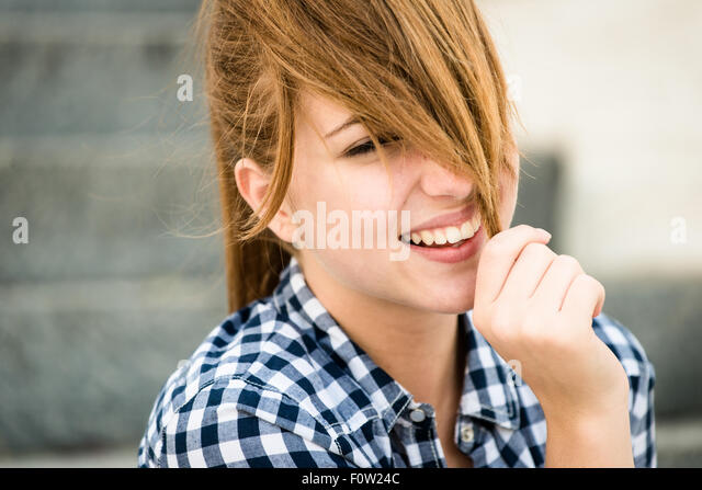 Teenager girl playing with her hair - outdoor on street - Stock Image