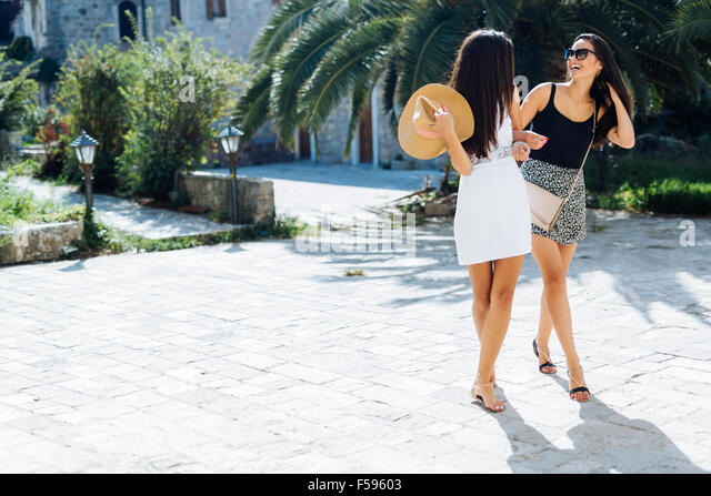 Two female friends sightseeing in summer while being on vacation - Stock-Bilder