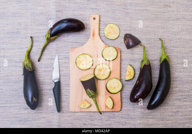 Slices of aubergine on chopping board, with knife and whole aubergines, overhead view - Stock Image