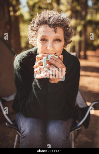 Portrait of a happy senior woman drinking coffee while sitting outside a tent and looking at camera. Mature caucasian - Stock Image