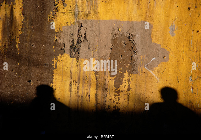 Yellow wall with silhouettes of two people - Stock-Bilder