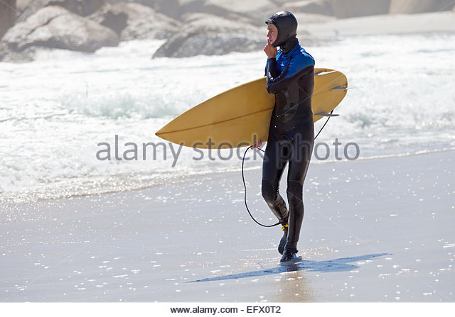 Surfer carrying surf board, walking along beach - Stock Image
