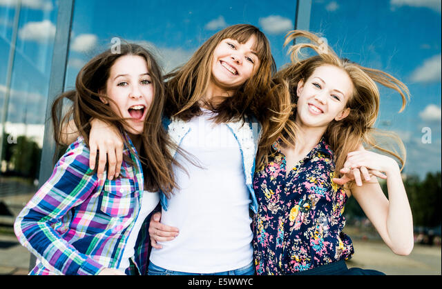 Three young women shaking hair in a row - Stock Image