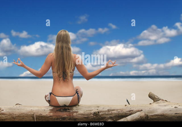 Pretty Woman Meditating on the Beach - Stock Image