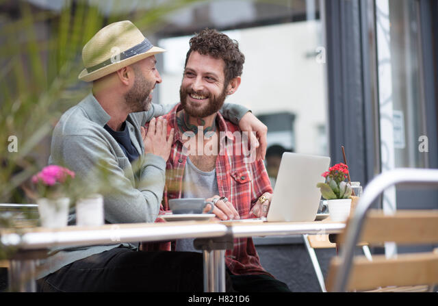 Gay couple sat sharing laptop in cafe - Stock-Bilder