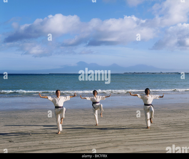 People performing White Crane Silat, an ancient martial art now used for exercise, on Jimbaran Beach, Bali, Indonesia - Stock-Bilder