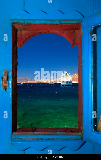 A view through the window from one of the old houses right by the sea in the Hora of Myconos, Greece - Stock-Bilder