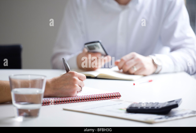 Business meeting taking notes and receiving email - Stock-Bilder
