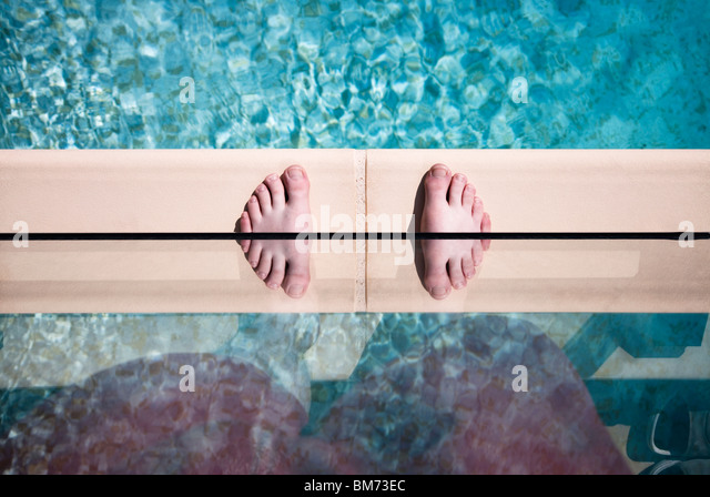 someones feet on the edge of a swimming pool against glass with a reflection making twin feet - Stock Image