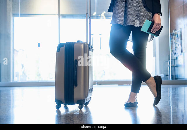 Hispanic woman holding passport standing with suitcase in airport - Stock Image