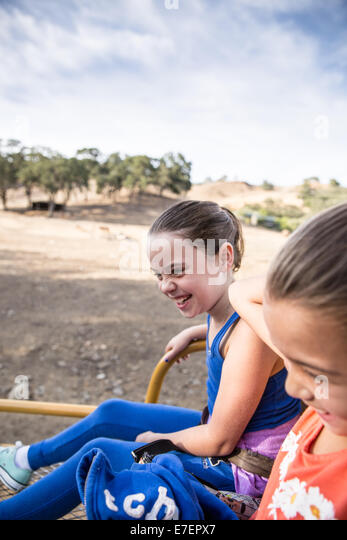 Girls smiling in a safari truck - Stock Image
