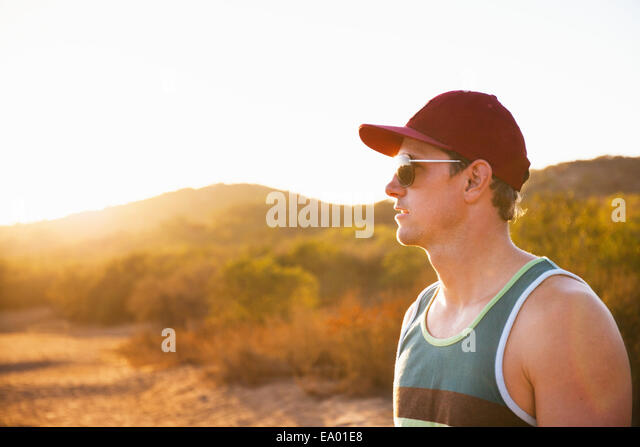 Male jogger in sunglasses and baseball cap, Poway, CA, USA - Stock Image
