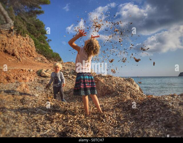 Kids throwing seaweed - Stock Image