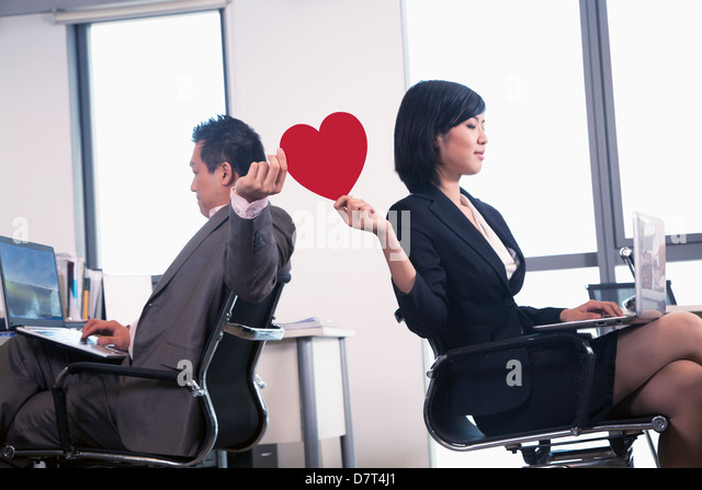 Work romance between two business people holding a heart - Stock-Bilder