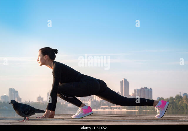 Young pretty fitness woman exercises on pier during morning sport training workout - Stock-Bilder