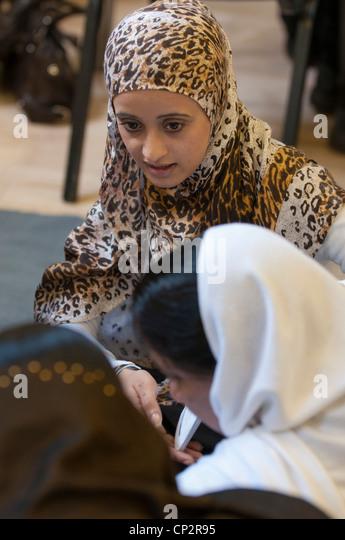 Asian women leading a group in a community center - Stock-Bilder