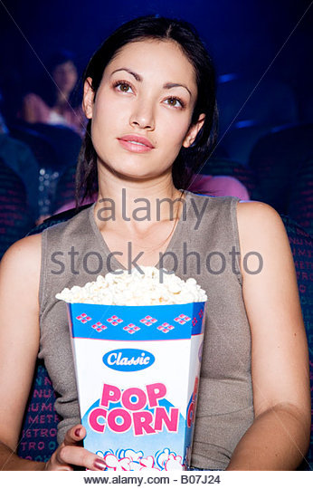 Woman watching a film at the cinema with a box of popcorn on her lap - Stock-Bilder