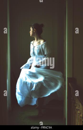 young woman dancing in an old house wearing white long romantic dress - Stock-Bilder